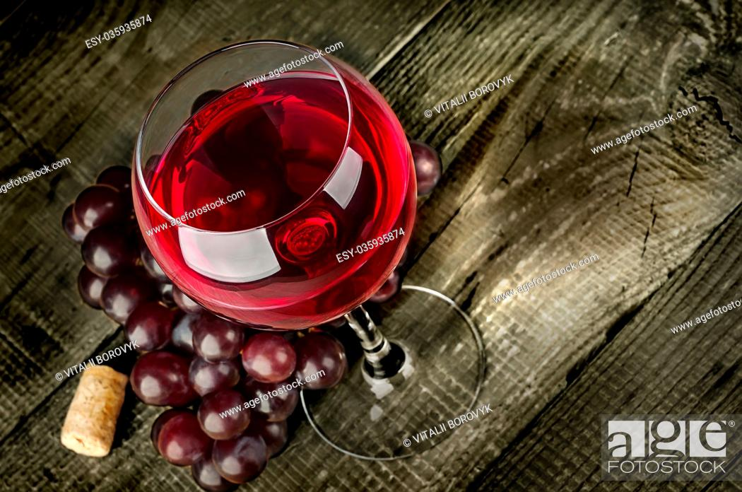 Stock Photo: Glass of red wine with grapes on a wooden table.