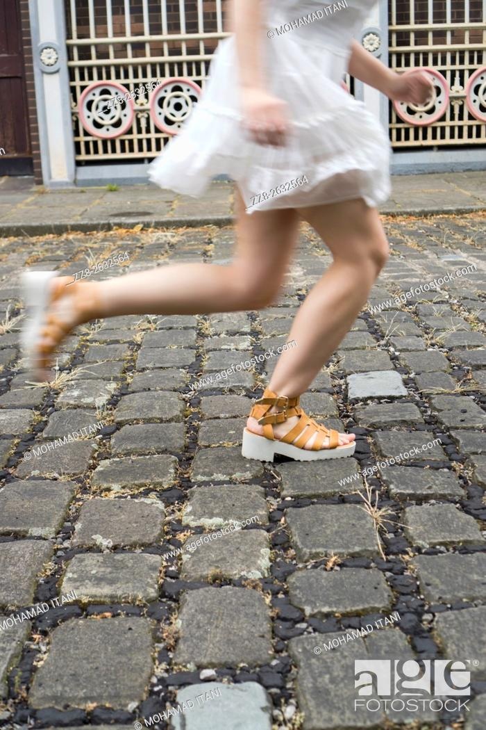 Stock Photo: Woman running on a cobbled street.