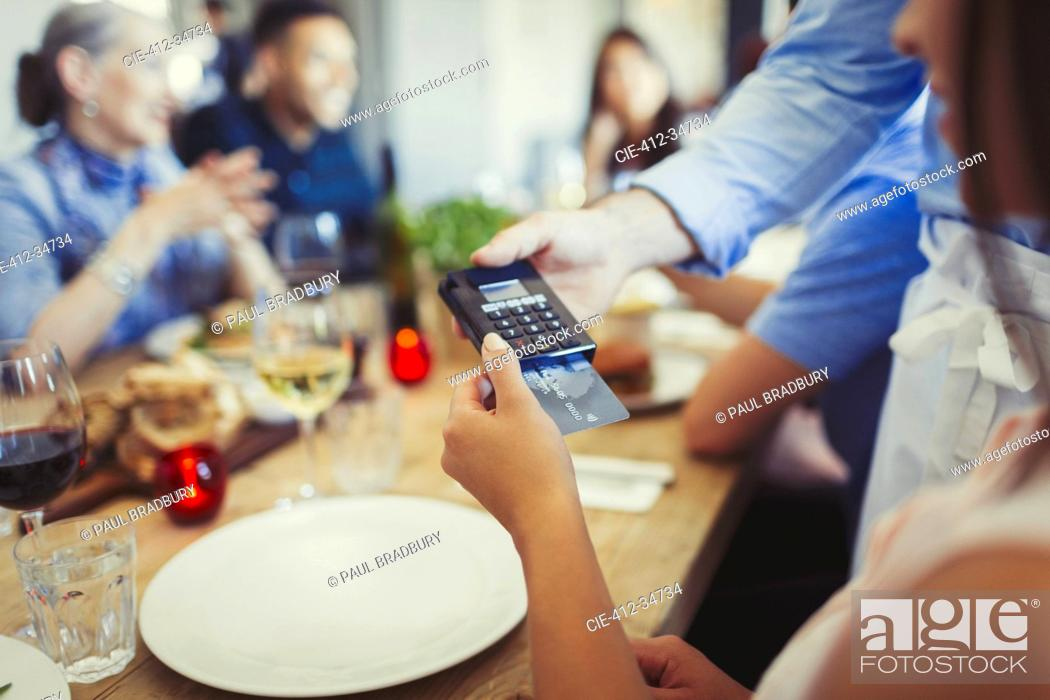 Stock Photo: Woman with credit card paying waiter, using credit card reader at restaurant table.