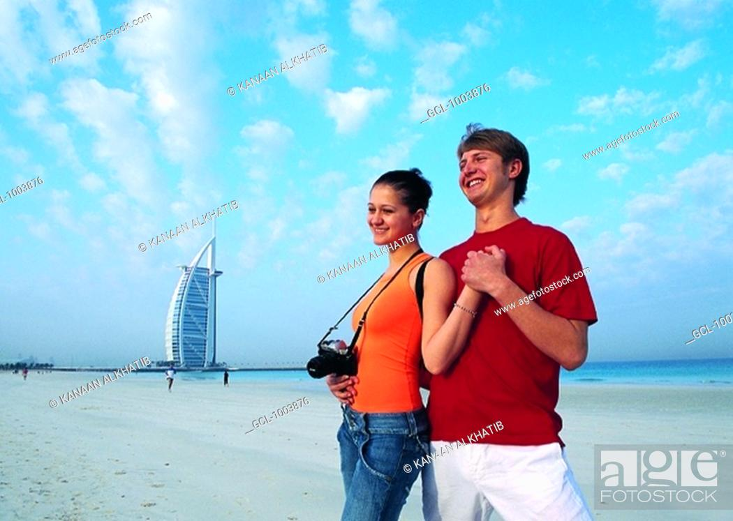 Stock Photo: Western tourists on the beach near Burj Al Arab hotel in Dubai, UAE.