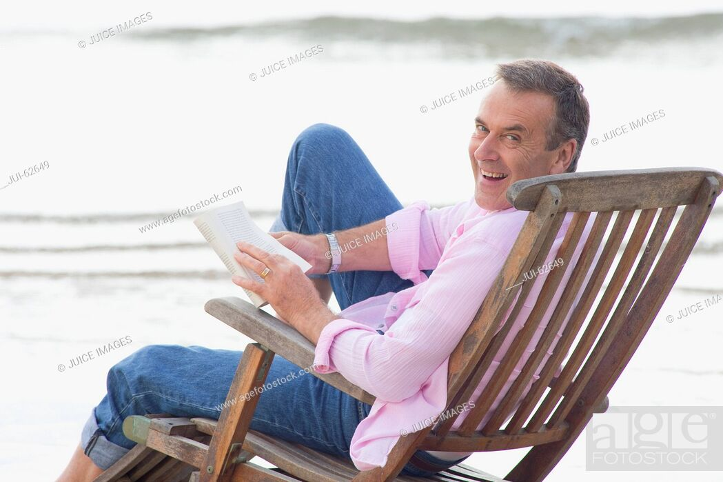 Stock Photo: Older man reading book in deck chair on beach.