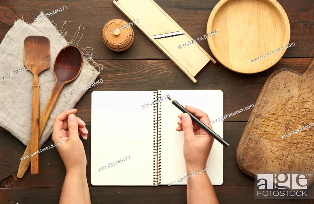 Stock Photo: open notebook with blank white sheets and kitchen utensils on a brown wooden table, female hands hold a black pencil, top view.