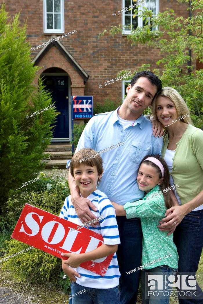 Stock Photo: Family of four outside house, boy 8-10 with 'for sale' sign, smiling, portrait.