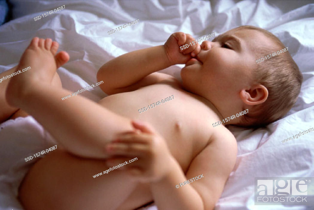 Stock Photo: Baby boy sucking his thumb lying on a bed.
