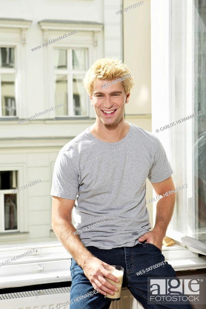 Stock Photo: Germany, Berlin, Young man sitting at open window, smiling.
