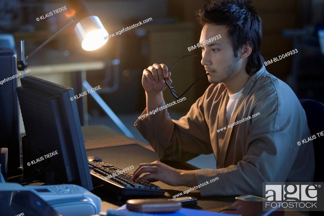 Stock Photo: Asian businessman typing on computer.