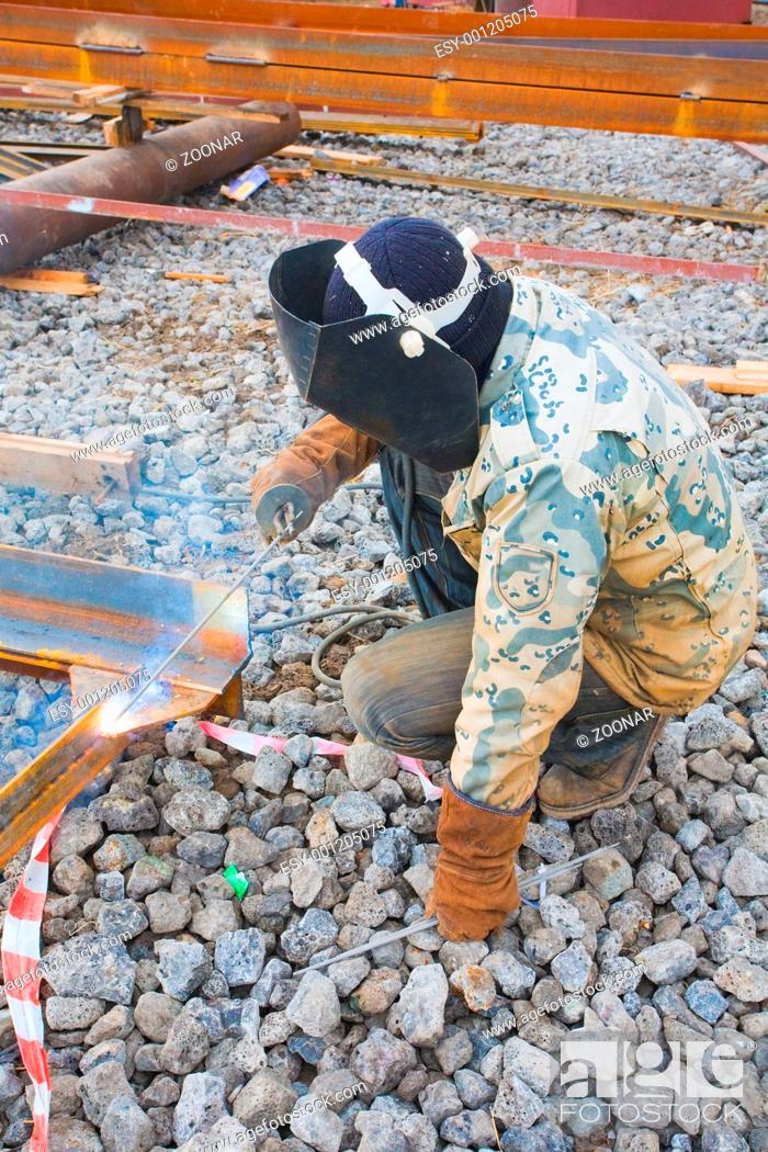 Stock Photo: Welder in protective mask welding metal construction on open air.