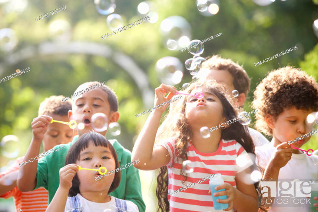 Stock Photo: Children outdoors blowing bubbles.