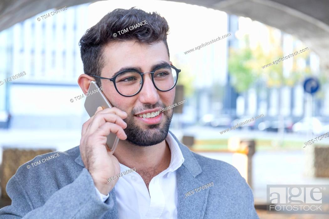 Stock Photo: Portrait of smiling young businessman on the phone.