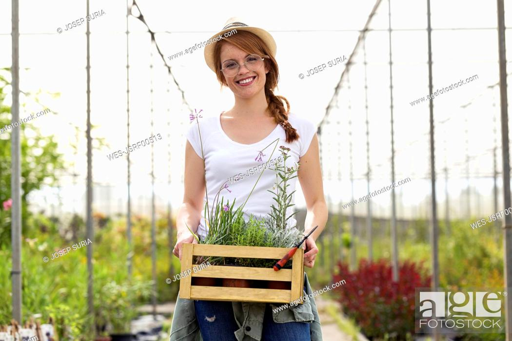 Stock Photo: Portrait of beautiful young woman holding wooden box with plants in the greenhouse.