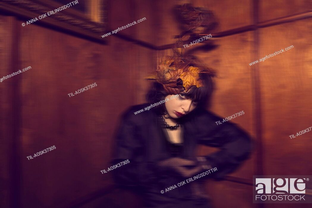 Stock Photo: Female wearing black with maple leaves in her hair.
