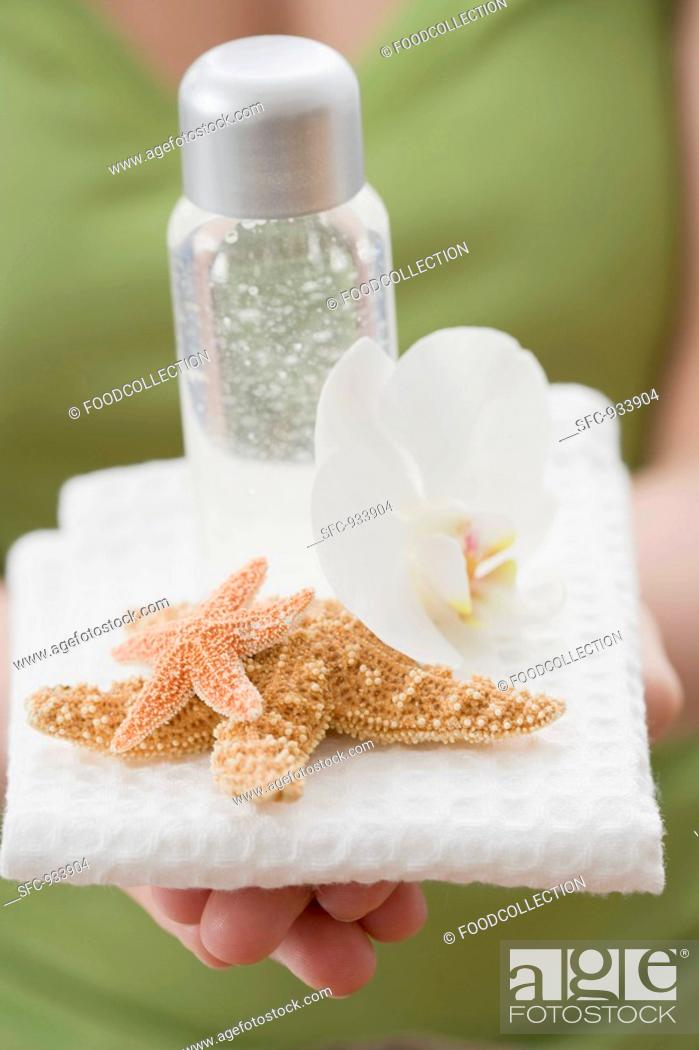 Stock Photo: Young woman balancing a small bottle of gel.