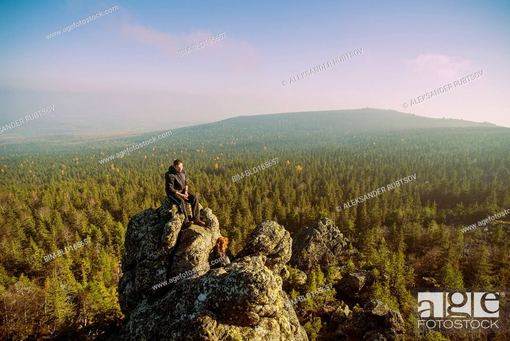 Stock Photo: Caucasian hikers admiring view from remote rock formation.