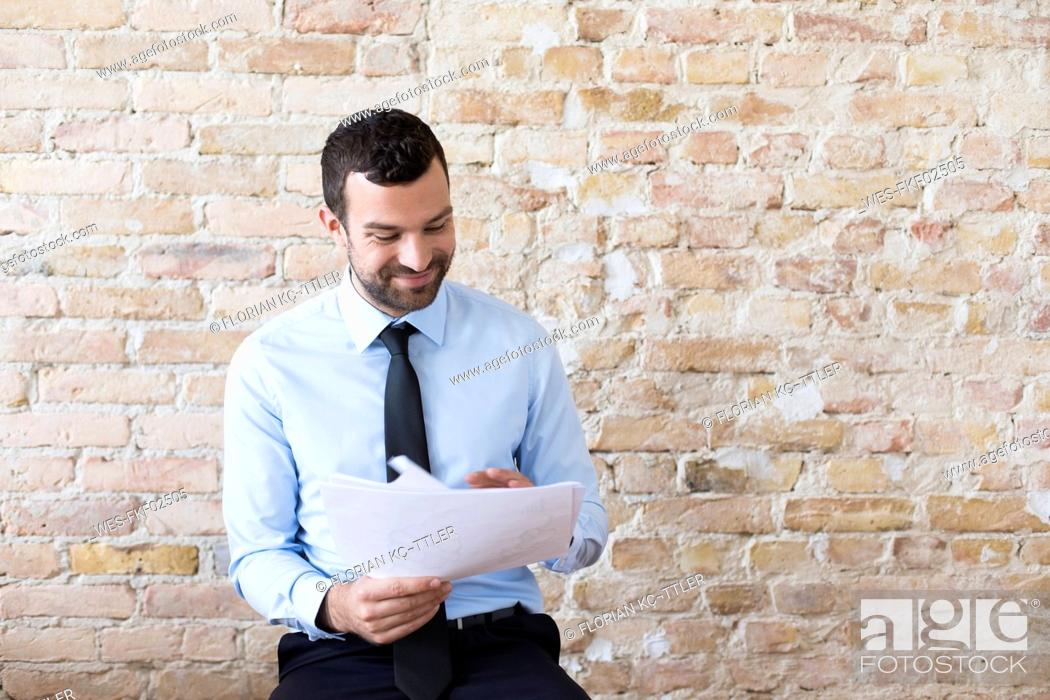Stock Photo: Smiling businessman reading document at brick wall.