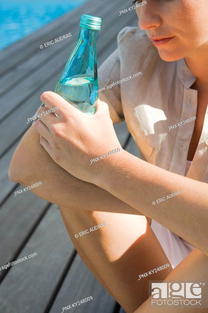 Stock Photo: Woman sitting on a boardwalk and holding a water bottle.
