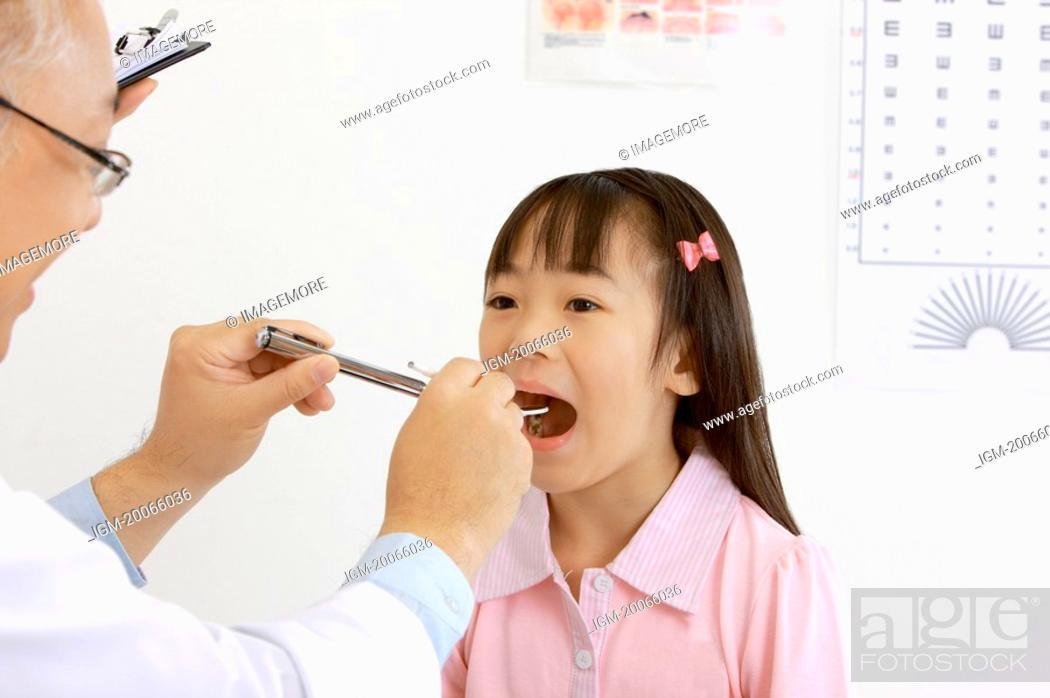 Stock Photo: Doctor checking little girl's teeth with medical equipment.