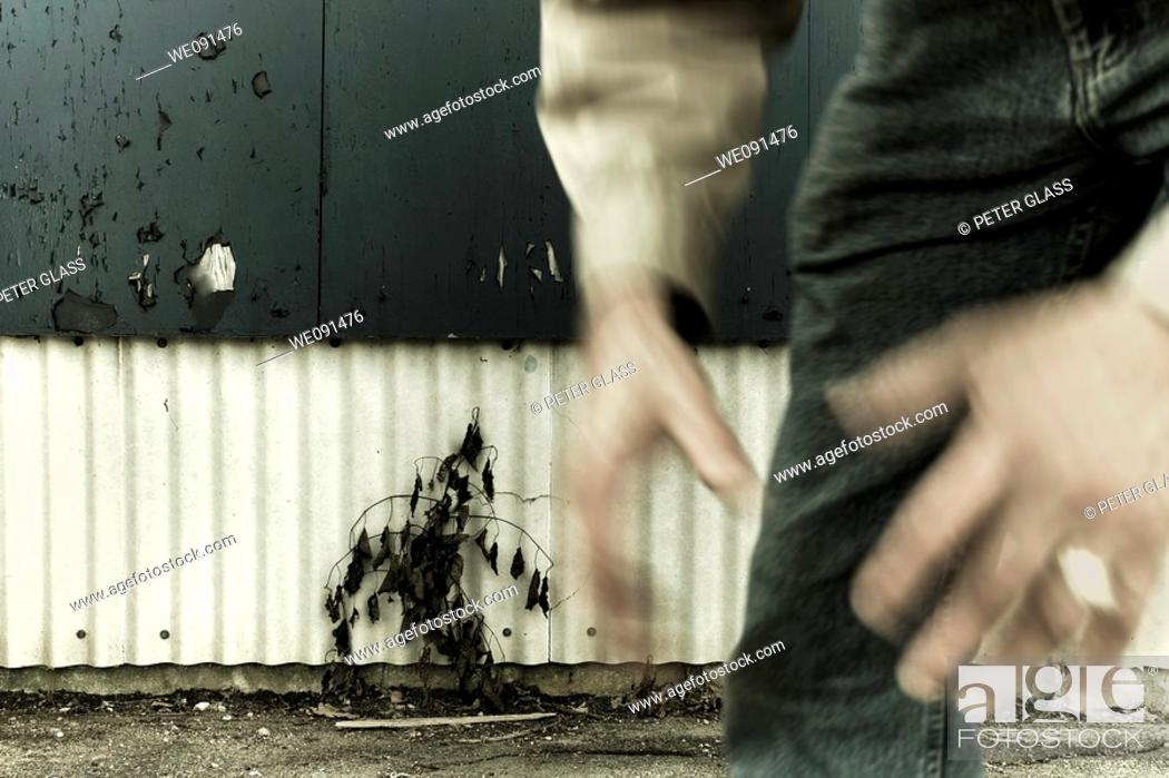 Stock Photo: Man in front of an outdoor wall with peeling paint.