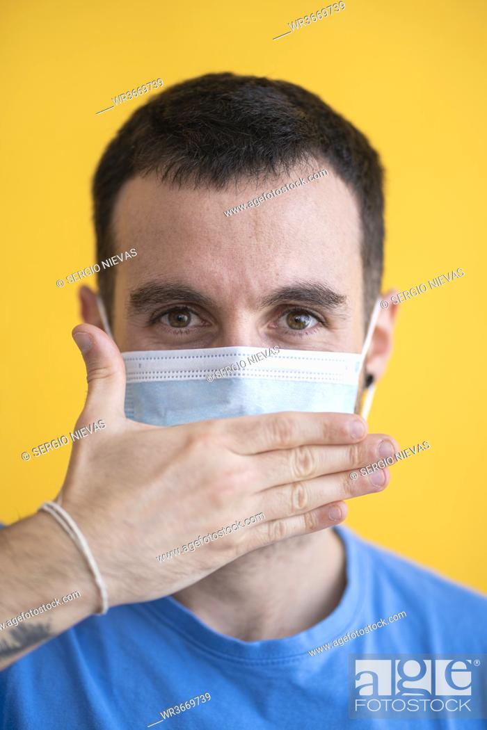 Stock Photo: Close-up of mid adult man wearing mask covering mouth with hand against yellow background.