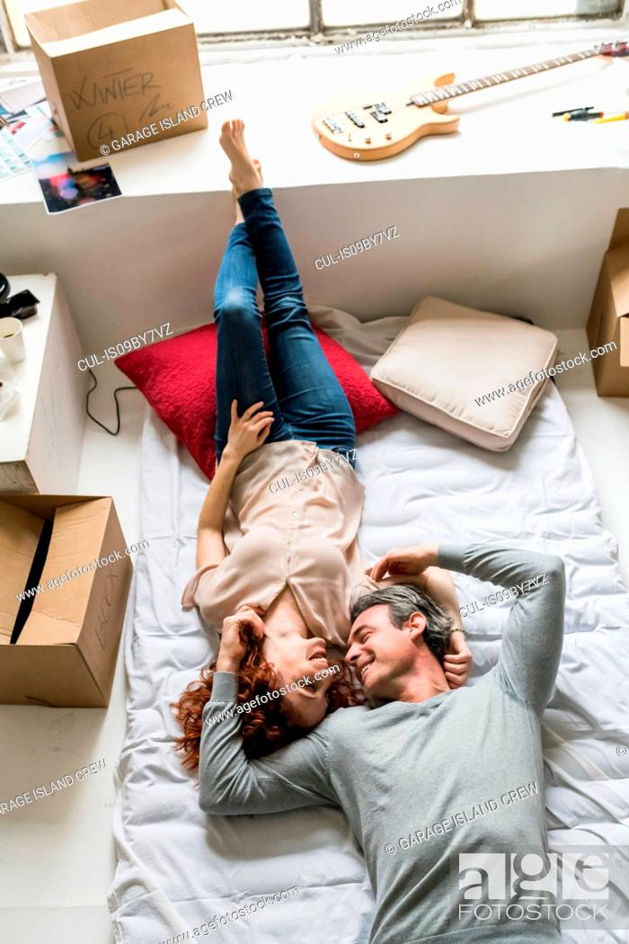 Imagen: Couple moving into apartment, lying face to face on mattress, overhead view.