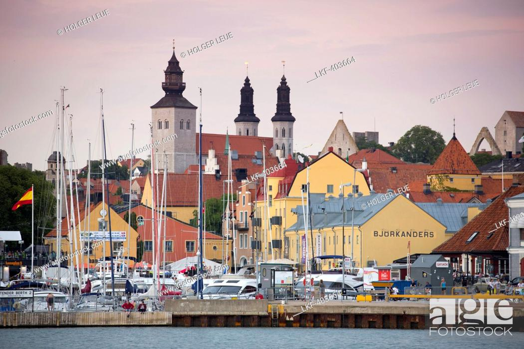 Stock Photo: Sailing boats at marina, colourful buildings and Domskyrkan cathedral at dusk, Visby, Gotland, Sweden, Europe.