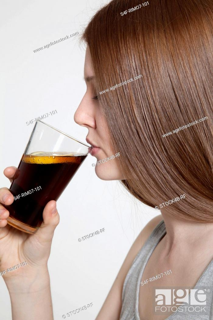 Stock Photo: Brunette young woman drinking cola.