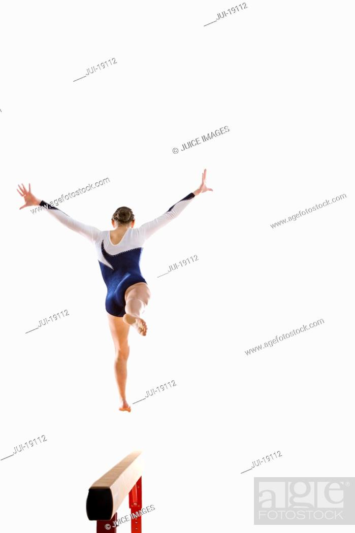 Stock Photo: Female gymnast performing jump on balance beam, rear view.