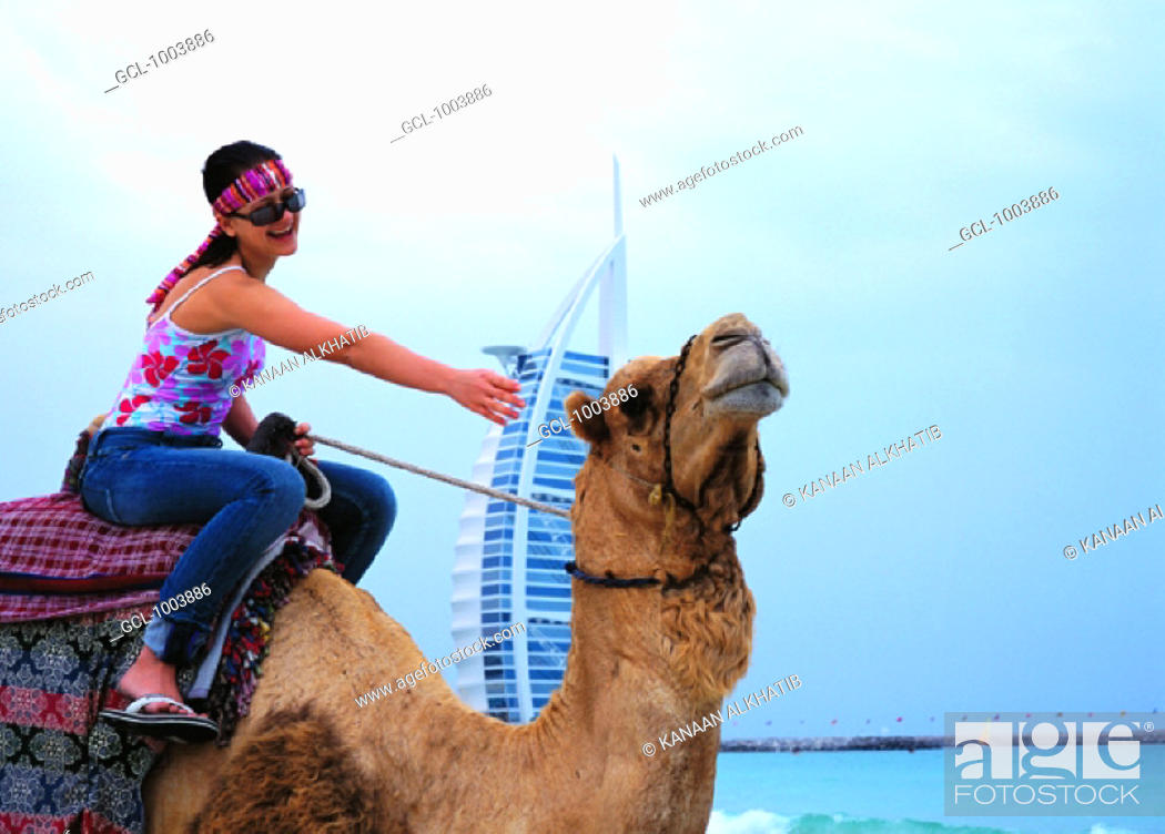Stock Photo: Western woman riding a camel on the beach in Dubai, United Arab Emirates.