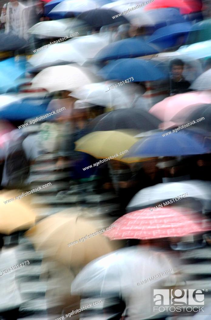 Stock Photo: Many umbrellas in the rain in central Tokyo Japan - motion blur.