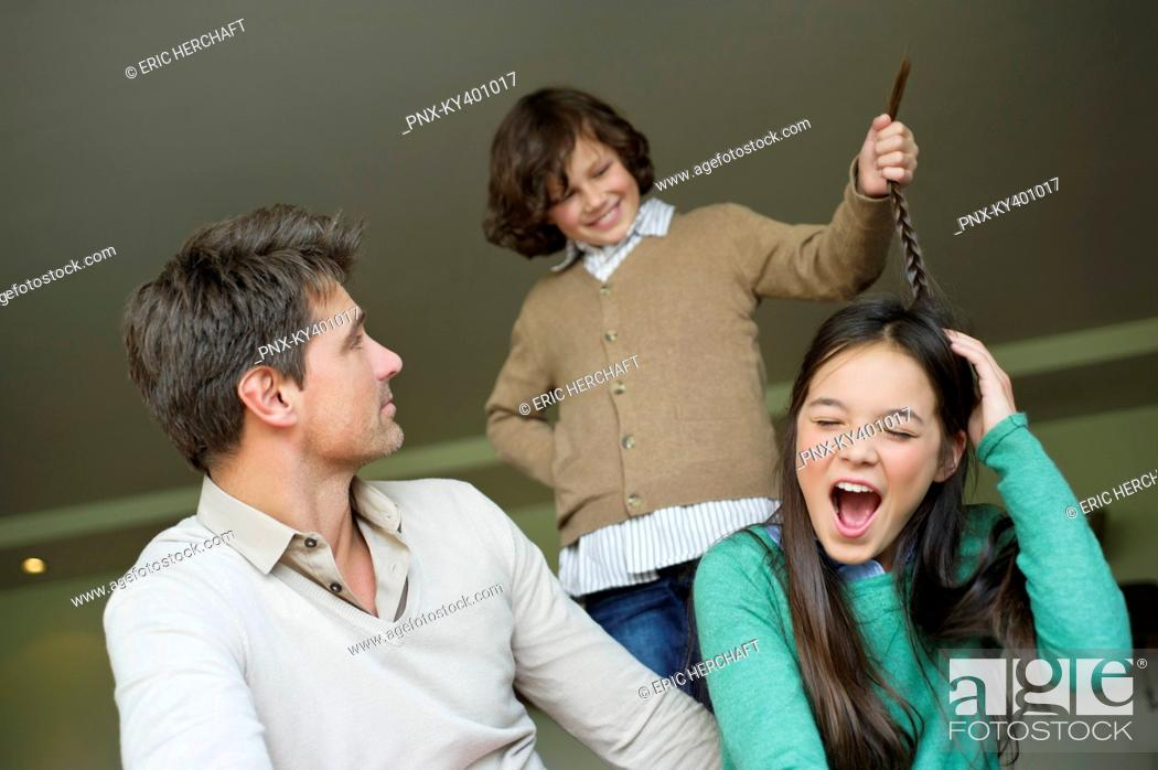 Stock Photo: Boy pulling his sister's braid with his father looking at him.
