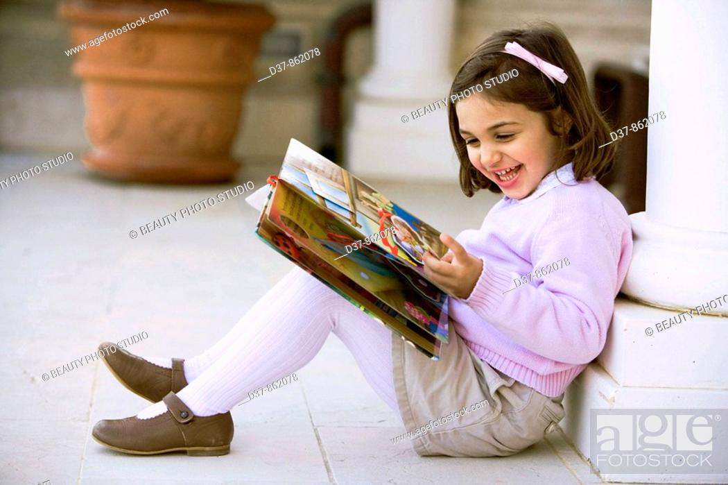 Stock Photo: Little girl reading a book at home.