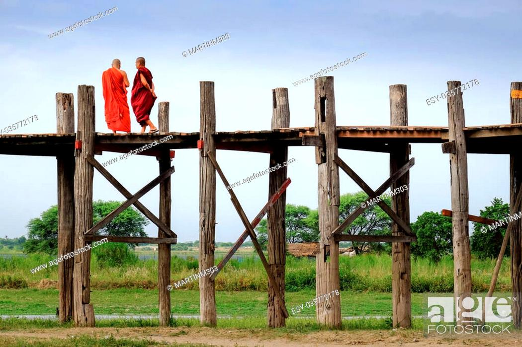 Stock Photo: Amarapura, Myanmar - 28 June, 2015: Two monks in colorful robes walk on wooden bridge, Amarapura, Mandalay, Myanmar.