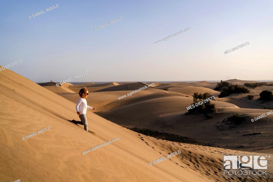 Stock Photo: Girl running down sand dune, Gran Canaria, Spain.