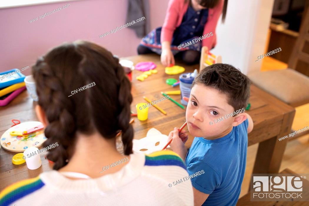 Stock Photo: Portrait cute boy with Down Syndrome coloring at table with siblings.
