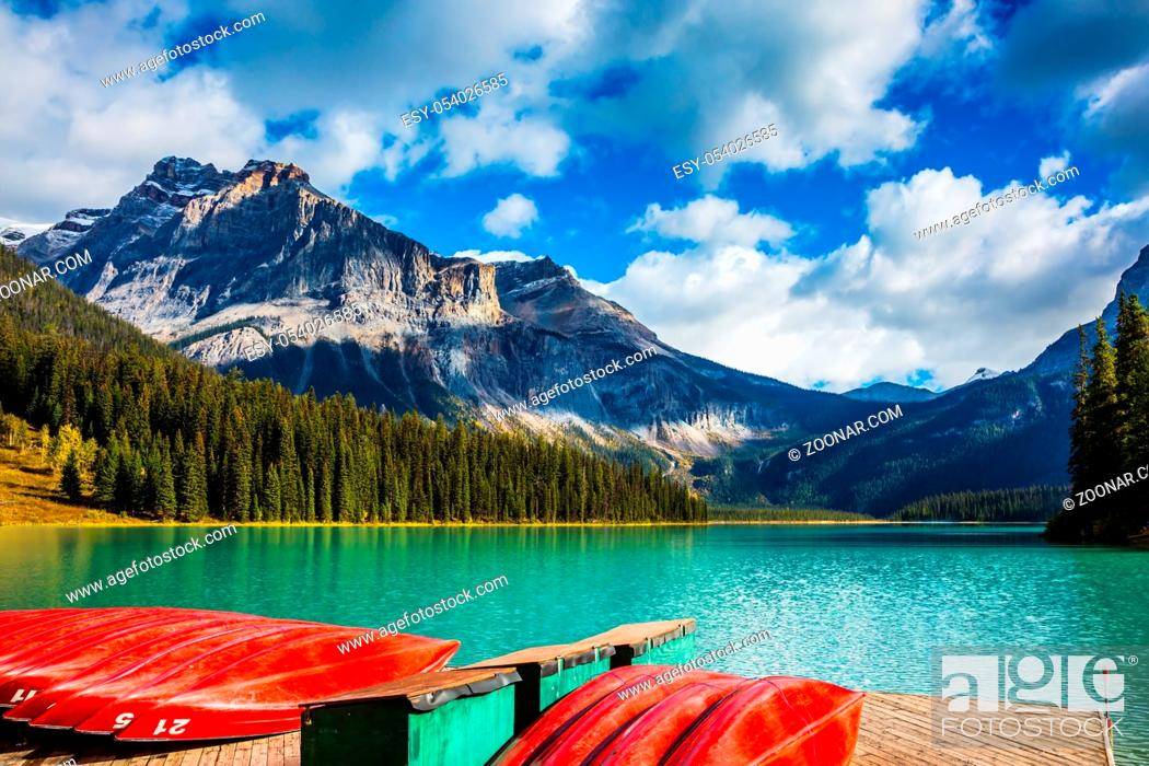 Stock Photo: Shiny red kayaks are dried upside down. Emerald Lake in the Canadian Rockies. The concept of leisure and tourism.