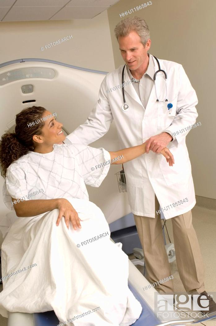 Stock Photo: Portrait of radiologist about to perform cat scan on female patient.