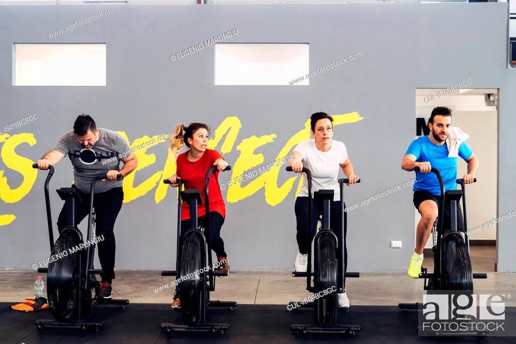 Stock Photo: People in gym using exercise bikes.