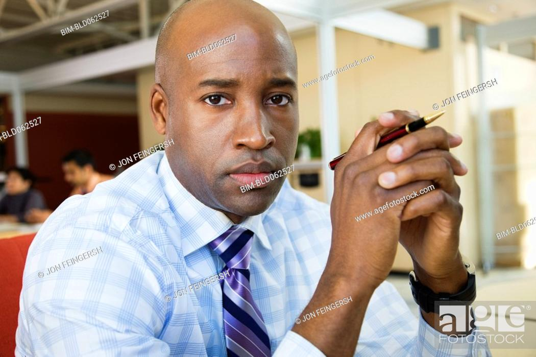 Stock Photo: African businessman looking serious in office.