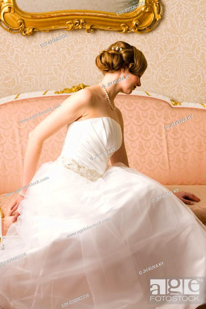 Stock Photo: Beautiful bride sits on the pink couch.
