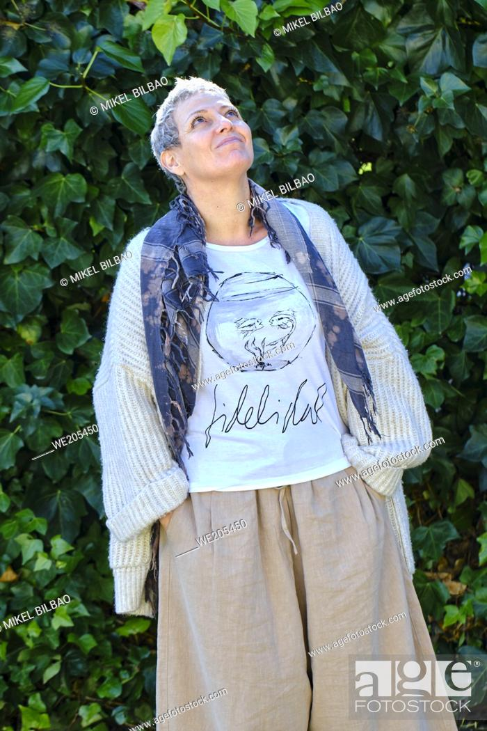 Imagen: Mature pretty caucasian woman with gray short hair and casual clothes posing outdoor in a garden with a leaves background.