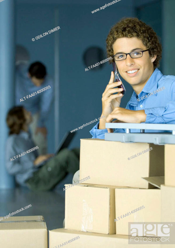 Stock Photo: Young man using cell phone, cardboard boxes in foreground.