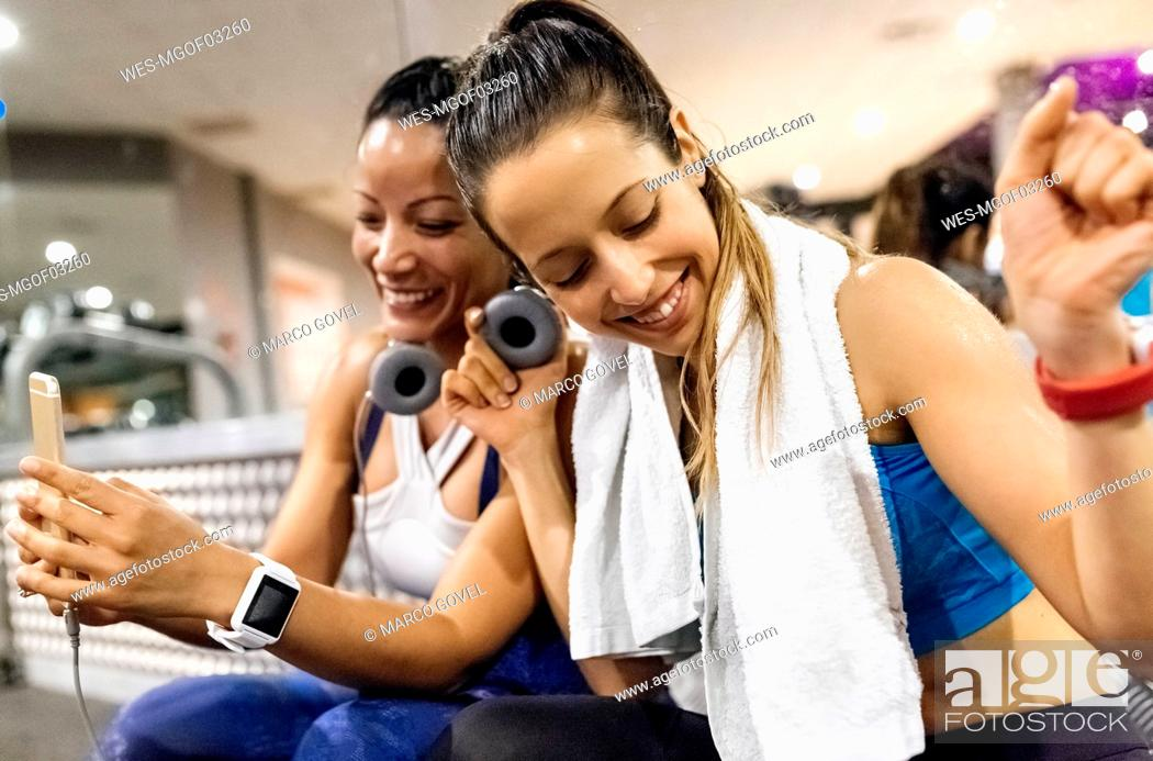 Stock Photo: Two women having fun with their smartphone after work out in the gym.