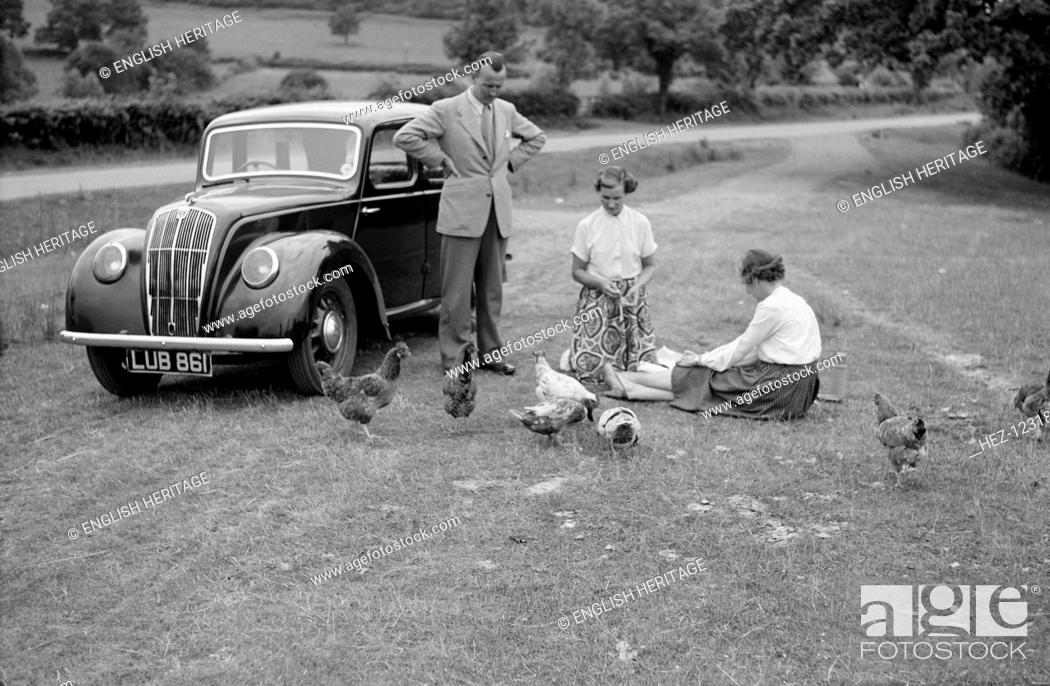Photo de stock: A family group feed chickens beside their car in the countryside, c1945-c1965.