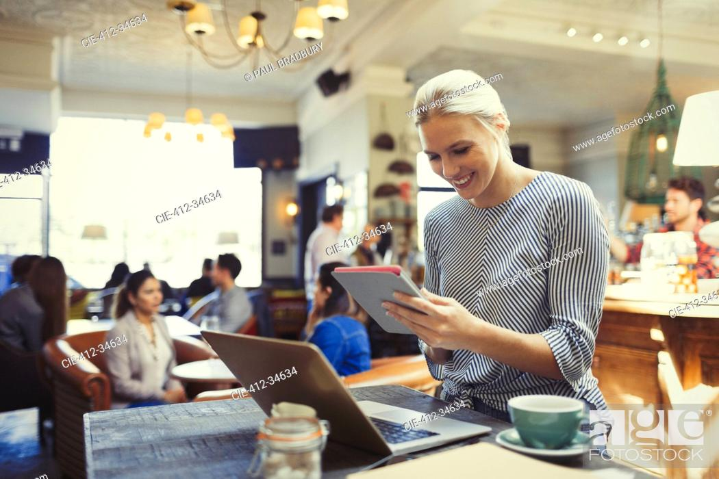 Stock Photo: Smiling creative businesswoman using digital tablet and laptop in cafe.