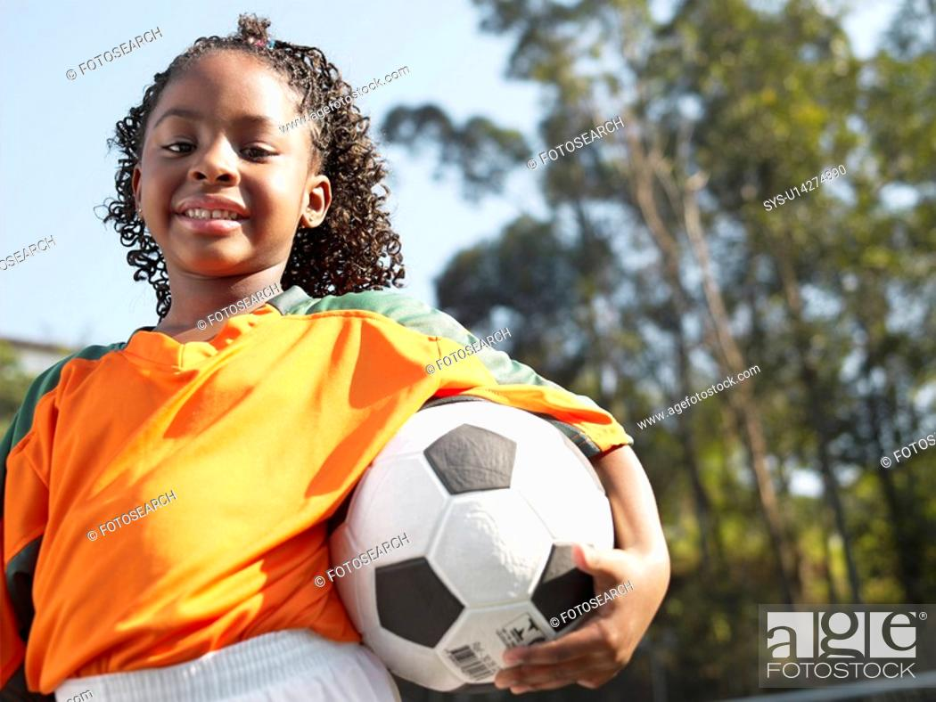 Stock Photo: Girl holding soccer ball portrait, low angle view.