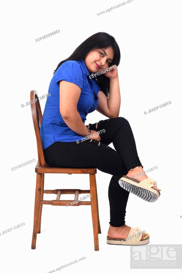 Photo de stock: portrait of a latin woman sitting on a chair in white background, side view, looking at camera, arms crossed and hand on faece.