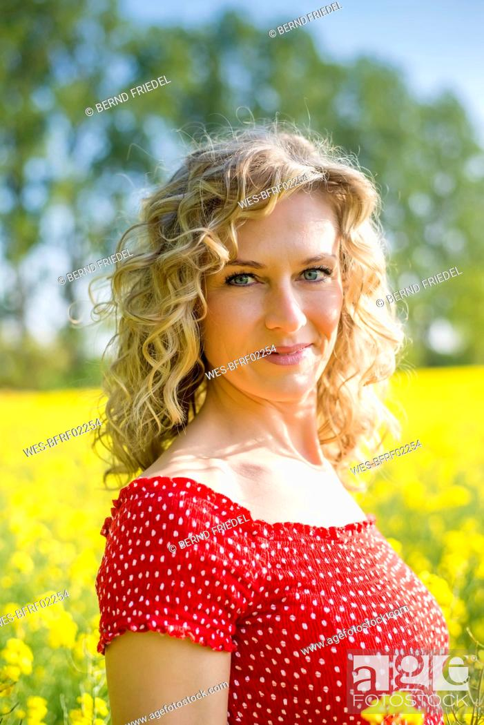 Stock Photo: Close-up of beautiful woman wearing red dress standing against oilseed rapes.