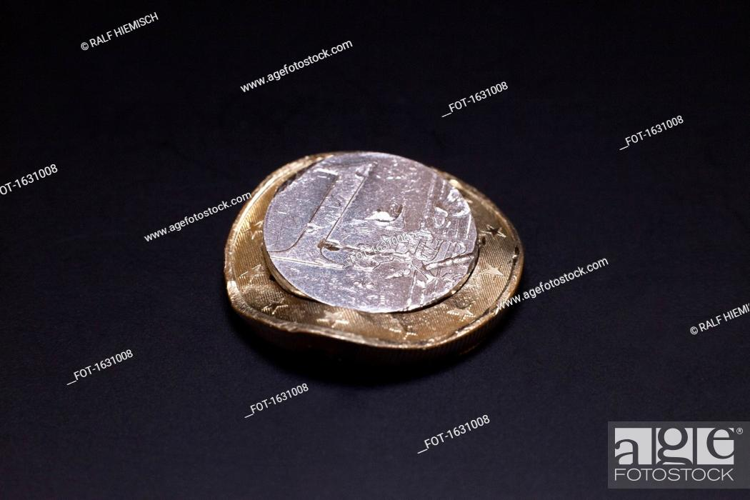 Stock Photo: Close-up of dented one Euro coin against black background.