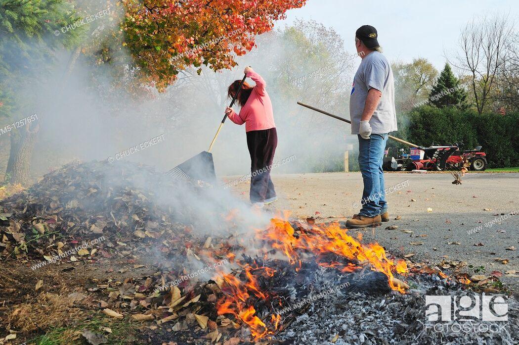 Stock Photo: Couple raking and burning autumn leaves.