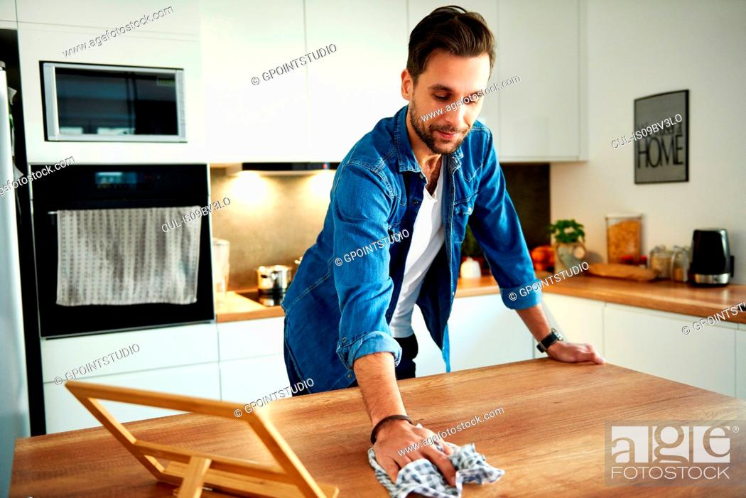 Stock Photo: Man wiping table in kitchen.