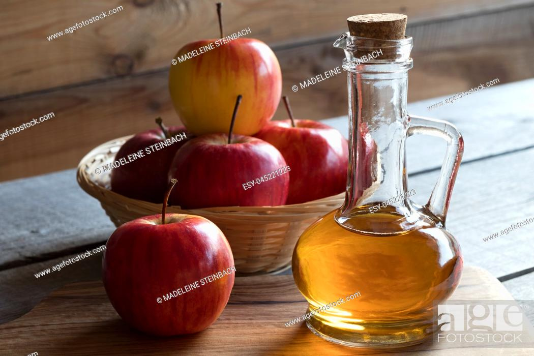 Stock Photo: A bottle of apple cider vinegar with apples in the background.